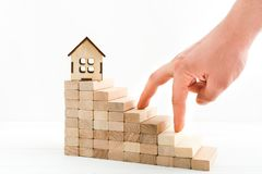 与木台阶、玩具的房子和去男性的手的企业和不动产概念在楼上 库存照片