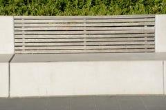 与木后面架靠背的石凳 免版税库存图片