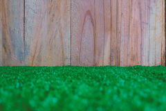 与木墙壁的塑料人为绿草 免版税库存照片