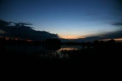 与木头的镇静池塘表面在与黎明和雾的好的日出 免版税库存照片