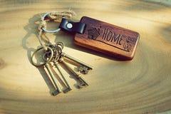 与木家庭钥匙圈的古色古香的房子钥匙 免版税库存图片
