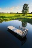 与木平台的农村夏天风景在河和绿色草甸有生长柳树的 免版税图库摄影