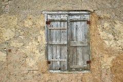 与木快门和传统黏土墙壁的减速火箭的窗口 库存图片