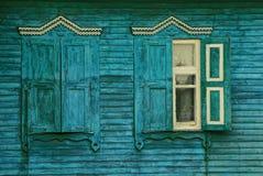 与木快门的两个老窗口在一个农村房子的绿色墙壁上 免版税库存照片