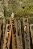 与木愿望的小菩萨小雕象在森林寺庙 图库摄影
