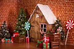 与木房子、糖果、树和礼物的圣诞节内部 没有人民 背景上色节假日红色黄色 免版税库存照片
