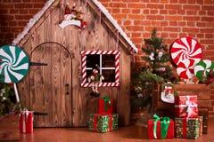 与木房子、糖果、树和礼物的圣诞节内部 没有人民 背景上色节假日红色黄色 库存照片