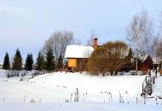 与木房子和一个冻池塘的农村风景 免版税库存照片