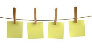 与木晒衣夹的黄色稠粘的笔记 免版税库存照片