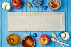 与木板、蜂蜜和苹果的犹太假日Rosh Hashana背景在桌上 在视图之上 图库摄影