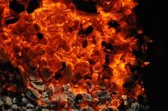 与木柴和燃烧的火焰闷燃的片断的充满活力的红色橘黄色发火焰纹理  篝火特写镜头在黑暗中 免版税库存照片