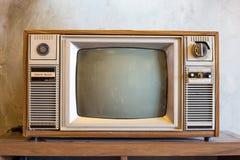 与木案件的减速火箭的电视在有葡萄酒墙纸的屋子里 免版税库存图片
