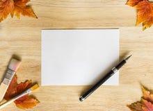 与木桌和秋季叶子的背景纹理 框架,做由笔、画笔、秋叶和白皮书 图库摄影