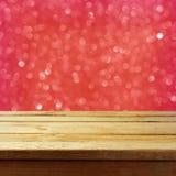 与木桌的圣诞节抽象背景和红色bokeh闪烁 免版税库存图片