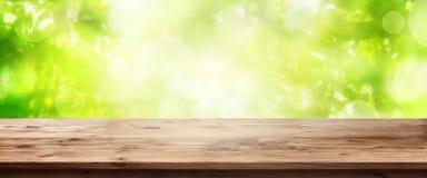 与木桌的抽象绿色背景 图库摄影
