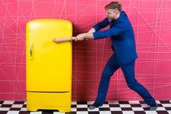 与木棒减速火箭的葡萄酒黄色冰箱的人正式典雅的衣服敲打 饥饿的学士要在冰箱附近吃 库存照片