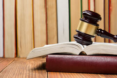 与木法官惊堂木的法律书籍在桌上在法庭或执法办公室 免版税库存图片