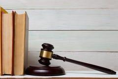 与木法官惊堂木的法律书籍在桌上在法庭或执法办公室 库存图片