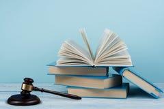 与木法官惊堂木的法律概念开放书在桌上在法庭或执法办公室,蓝色背景 复制 库存照片