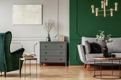 与木洗脸台、斯堪的纳维亚沙发和鲜绿色扶手椅子的时兴的客厅内部 免版税库存图片