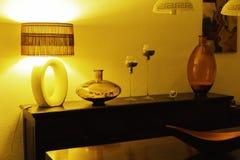 与木洗脸台、葡萄酒灯、花瓶和烛台的室内部对在夜间照明设备的轻的墙壁 内部 库存照片
