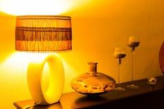 与木洗脸台、葡萄酒灯、花瓶和烛台的室内部对在夜间照明设备的轻的墙壁 内部 免版税库存图片