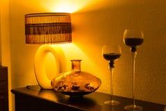 与木洗脸台、葡萄酒灯、花瓶和烛台的室内部对在夜间照明设备的轻的墙壁 图库摄影