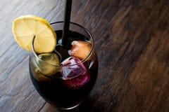 与木炭、柠檬和五颜六色的泡影冰块的黑柠檬水 库存图片