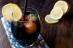 与木炭、柠檬和五颜六色的泡影冰块的黑柠檬水 免版税图库摄影