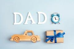 与木玩具汽车,礼物盒,警报cloc的父亲节背景 免版税库存照片