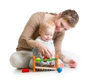 与木玩具的母亲和婴孩戏剧 库存照片