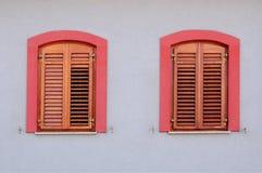 与木百叶窗的两个红色窗口在白色墙壁上 免版税库存照片