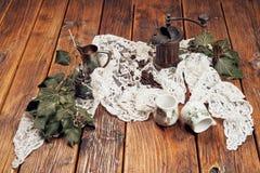 与木研磨机,咖啡豆的静物画,与一个小金属咖啡罐和一棵金属糖杯子和常春藤在一张老木桌上 免版税库存图片