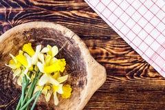 与木碗和厨房布料的美丽的黄色水仙在木背景,春天黄水仙 免版税库存图片
