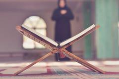 与木立场的一个开放圣洁古兰经与祈祷的人在背景中 免版税图库摄影