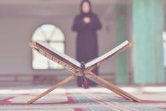 与木立场的一个开放圣洁古兰经与祈祷的人在背景中 免版税库存图片