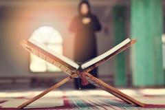 与木立场的一个开放圣洁古兰经与祈祷的人在背景中 库存照片