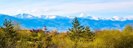 与木篱芭、树和多雪的山的春天风景 免版税库存照片