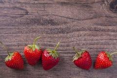 与木纹理的甜草莓背景的 图库摄影