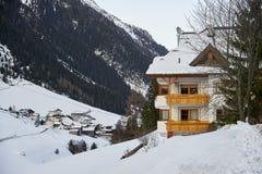 与木阳台的积雪的山瑞士山中的牧人小屋山的脚的在以后冬天 免版税库存照片