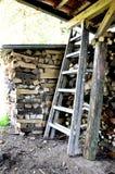 与木柴和老梯子的门廊 免版税库存照片