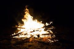 与木头的烧伤火在海滩阵营 库存图片