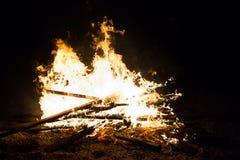 与木头的烧伤火在海滩阵营 免版税库存照片