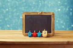 与木dreidel抽陀螺和黑板的犹太假日光明节背景在蓝色bokeh点燃 免版税库存图片