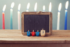 与木dreidel抽陀螺的犹太假日光明节在蜡烛的背景和黑板 免版税库存照片