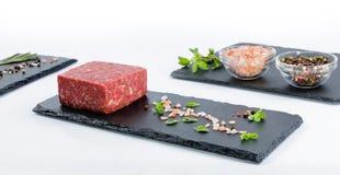 与未加工的绞细牛肉,整个胡椒片断的三个板岩板, 免版税图库摄影
