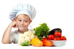 与未加工的蔬菜的逗人喜爱的在厨房里帮忙的仆人 免版税库存照片