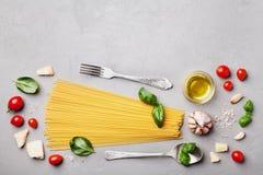 与未煮过的意粉、蕃茄、蓬蒿、乳酪、大蒜和橄榄油的意大利食物背景烹调的在灰色石桌上的面团 库存图片