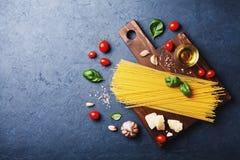 与未煮过的意粉、蕃茄、蓬蒿、乳酪、大蒜和橄榄油的意大利食物背景烹调的在黑暗的石桌上的面团 免版税图库摄影