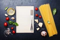 与未煮过的意粉、蕃茄、蓬蒿、乳酪、大蒜和橄榄油的意大利食物背景从上面烹调的在桌上的面团 免版税库存图片